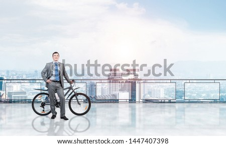 Happy man wearing business suit standing on balcony with bike. Businessman with bicycle on background of sky above megalopolis. Smiling cyclist holding bicycle on terrace with modern downtown view. #1447407398