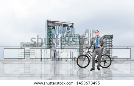 Happy man wearing business suit standing on balcony with bike. Businessman with bicycle on background of sky above megalopolis. Smiling cyclist holding bicycle on terrace with modern downtown view. #1453673495