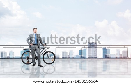 Happy man wearing business suit standing on balcony with bike. Businessman with bicycle on background of sky above megalopolis. Smiling cyclist holding bicycle on terrace with modern downtown view. #1458136664