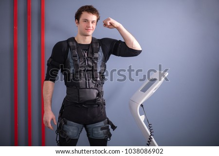 Happy man wearing EMS training suit standing near machine, muscle stimulation, showing biceps #1038086902