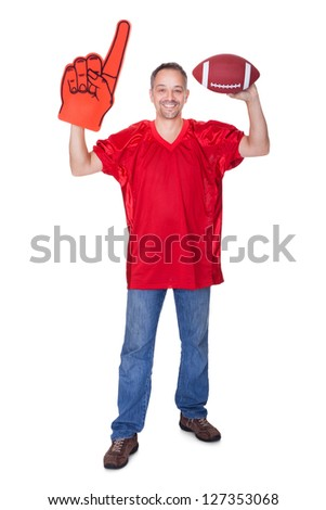Happy Man Wearing Foam Finger And Holding Rugby Ball On White Background