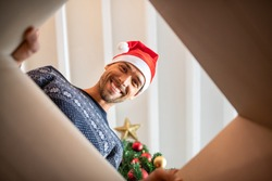 Happy man wearing xmas hat unpacking christmas gift. Young man smiling while opening present and looking inside. Portrait of guy opening cartboard box under the christmas tree while looking at camera.