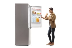Happy man with a sandwich standing in front of a fridge isolated on white background