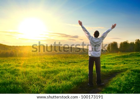 happy man with hands up on sunset background