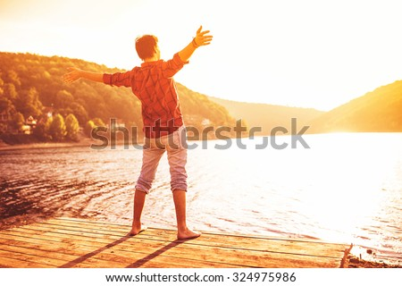 Happy man with hands up on sunset. Open arms, standing on a pier barefoot. Enjoying sun. Gazing sun.  Lens flare.