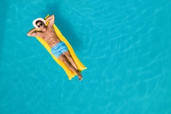 Happy man with inflatable mattress in swimming pool, top view and space for text. Summer vacation