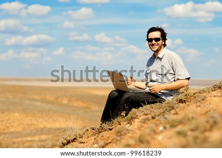 happy man with laptop on the hill