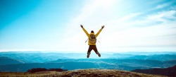 Happy man with open arms jumping on the top of mountain - Hiker with backpack celebrating success outdoor - People, success and sport concept
