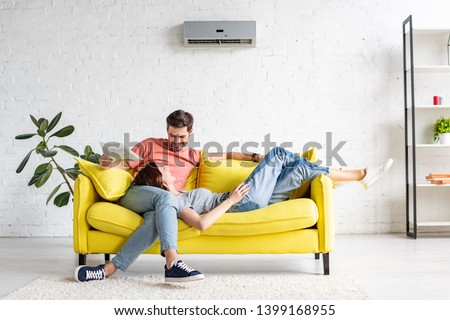 happy man with smiling girlfriend relaxing on yellow sofa under air conditioner at home