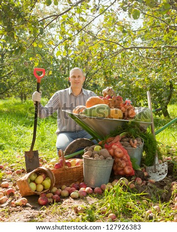 Happy man with vegetables harvest in garden