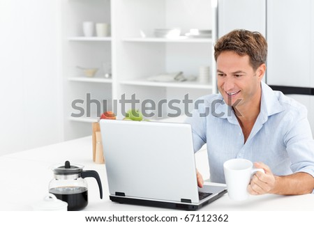 Happy man working on his laptop while drinking coffee in the kitchen