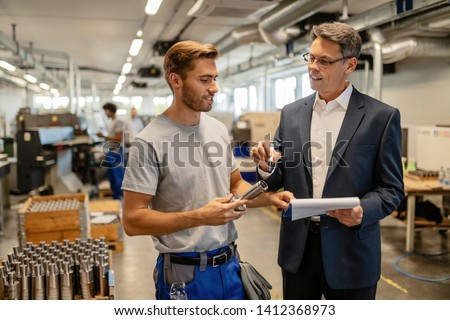 Happy manager and manual worker talking while examining manufactured products and analyzing reports in steel factory.