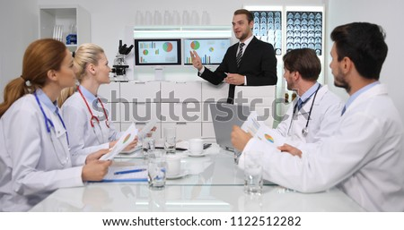 Happy Manager Man Positive Talking with Group of Medical Doctors Team About Pie Chart Data in Hospital Management Cabinet or Healthcare Center Meeting Room