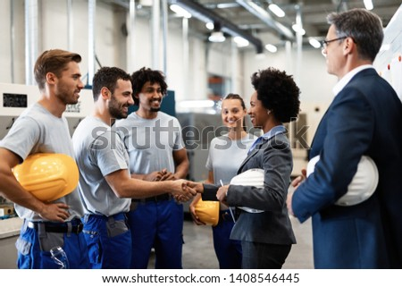 Happy manual worker handshaking with African American manager who is visiting factory with her colleague.