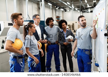 Happy manual worker presenting the results of business development while giving presentation to company leaders and his team in a factory.