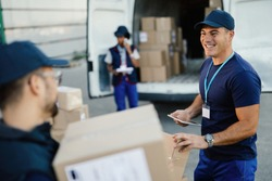 Happy manual worker using touchpad while communicating with his coworker and organizing package delivery.