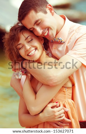 Happy marriage concept. Portrait of a beautiful laughing (smiling) couple of hipsters in trendy clothing. Wedding day. Close up. Outdoor shot