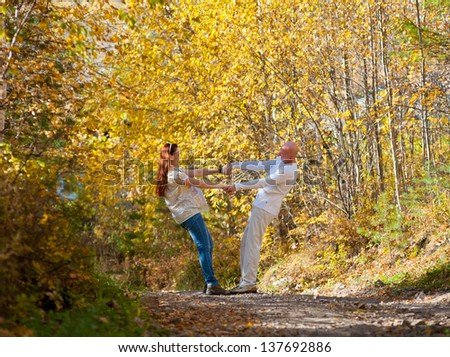 happy married couple - husband and his pregnant wife walk in autumn forest