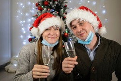 Happy married couple in protective masks drinks champagne for christmas. Family new year during quarantine covid 19 pandemic safe at home