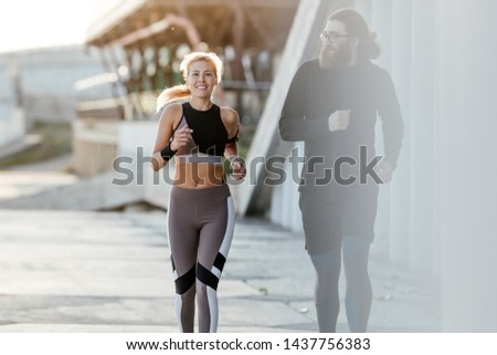 Happy married couple Jogging outdoors. Morning jog on the waterfront. Family leads a healthy lifestyle