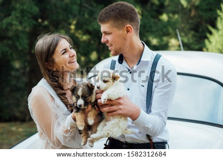 Happy married couple playing with little puppys. puppies for the wedding