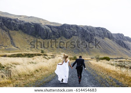 Happy married couple running down country road