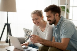 Happy married couple sitting in living room on couch at home, using computer purchasing online. Husband holding credit card customers making secure payment via internet. Technology, e-banking concept