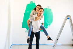 Happy married couple that just move into a new apartment or home. Good-looking man carrying a young woman on his back and smiling