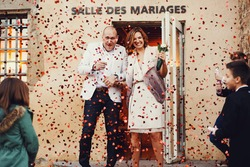 Happy married stylish bride and groom smiling out of the city hall ceremony Lyon holding hands showered with rose petals confetti
