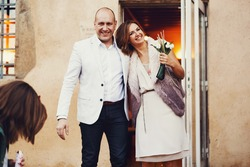 Happy married stylish bride and groom smiling out of the city hall ceremony Lyon holding hands