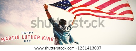 happy Martin Luther King day against low angle view of man holding american flag against cloudy sky #1231413007