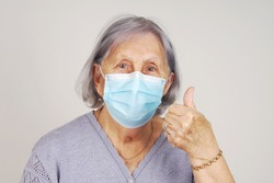 Happy masked senior woman with thumb up after receiving COVID vaccine