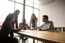 Happy mature and young multiracial employees listening to skilled 30s male team leader, developing corporate strategy together, brainstorming project ideas or analyzing research results in office.