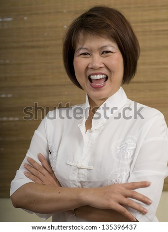 Happy mature Asian woman laughing