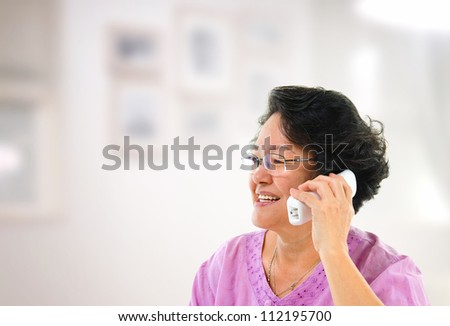 Happy mature Asian woman talking on phone, inside house