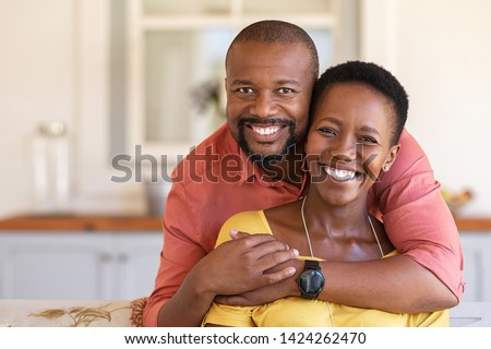 Happy mature black couple bonding to each other and smiling while sitting on couch. Portrait of smiling black man embrace his wife from behind and looking at camera.