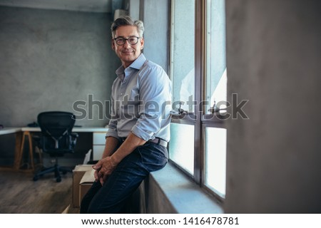 Happy mature businessman leaning by a window sill and staring to camera. Male entrepreneur at his office looking at camera.