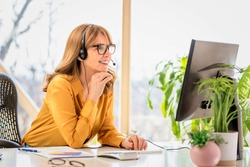 Happy mature businesswoman in headset speaking by conference call while looking at computer. Home office.