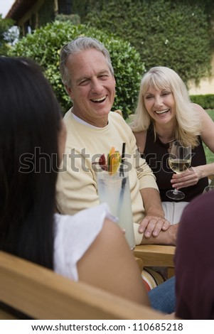 Happy mature Couple and female friend with drinks enjoying together