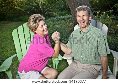 Happy mature couple arm wrestling outdoors. The woman is winning, the man is laughing.