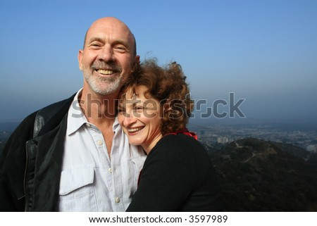 stock photo : Happy mature couple embracing outdoors ontop of a city.
