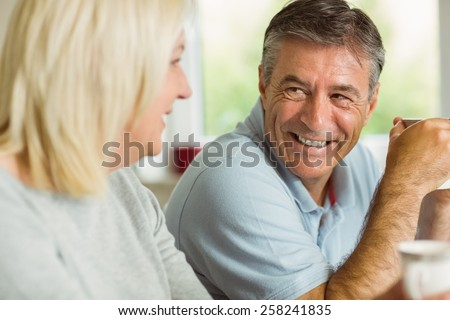 Happy mature couple having coffee together at home in the kitchen #258241835