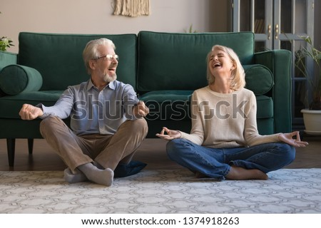 Happy mature couple having fun, practicing yoga together at home, laughing grey haired man and woman sitting in lotus pose on floor in living room, breathing, relaxing, healthy lifestyle concept