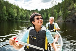 Happy mature couple in life vests canoeing in forest lake. Sunny summer day. Tourists traveling in Finland, having adventure.
