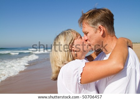 Happy mature couple kissing on a sunny day at the beach