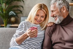 Happy mature couple laughing and drinking coffee while having fun at home