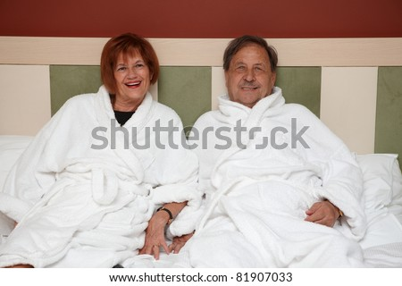 Happy mature couple laying on bed at wellness hotel, smiling, looking at camera.?