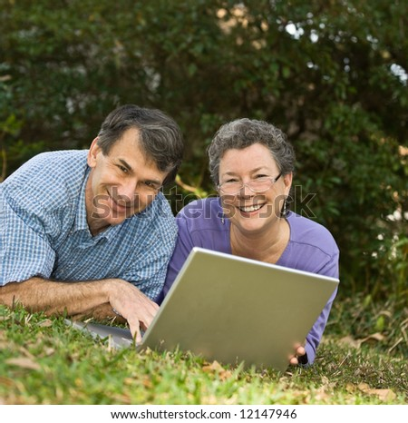 Happy mature couple lying in the grass and working on their laptop - stock photo