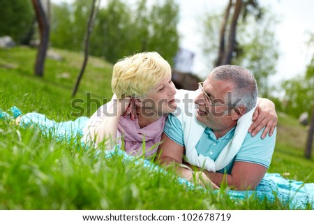 Happy mature couple lying on grass and looking at each other in the countryside