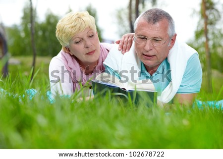 Happy mature couple lying on grass and reading a book in the countryside